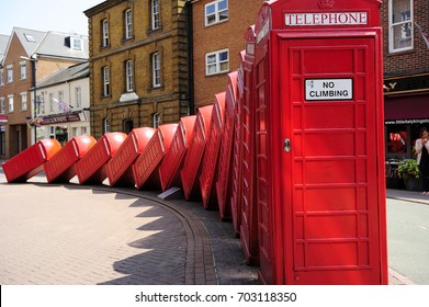 LONDON, ENGLAND- 11 JULY 2013: Out of Order, the sculpture involving 12 Red Phone boxes sometimes know as Tumbling Telephones. Kingston upon Thames  is an area of south west London, England