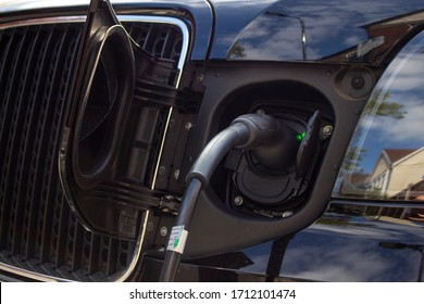 London, England - April 13 2020: Close up of an electric vehicle recharging point in a residential road with an electric Taxi plugged in charging.