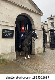 London, England; 18 February 2021 - Royal House guard at Parliament Square in Central London. A Palace guard sits in uniform on a dark brown horse.