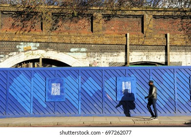 LONDON, ENGLAND- 22 DECEMBER 2013: Undefined man walking on the pavement and his shadow on the blue fence in front of the old brick building in Shoreditch high street, East London, England, UK