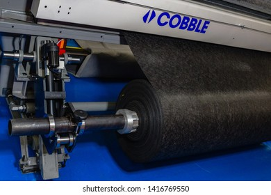 London, England, 22/05/2019 Cobble machine with rolls of material feeding through equipment for commercial production in a factory for textiles industry blue colourful floor metal bearings