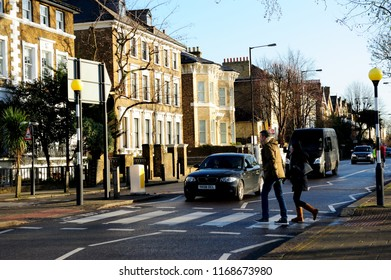 LONDON, ENGLAND- 24 JANUARY 2015: Undefined people in the street and the sunlight on the traditional English flat with leafless tree in East Hill, Wandsworth, South West London, England, UK