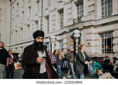 LONDON, ENGLAND - 25th October, 2018: Arab man walking between the crowd while read his mobile phone, across The Queen's Walk, in a sunny day in London, Uk.