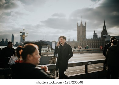 LONDON, ENGLAND - 25th October, 2018: Young man walking by Westminster Bridge sidewalk while calling by phone, with Westminster Palace in the background, in London, England.