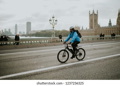 LONDON, ENGLAND - 25th October, 2018: Man riding in a mountain bike by Westminster Bridge, with Westminster Palace in the background, in London, United Kingdom.