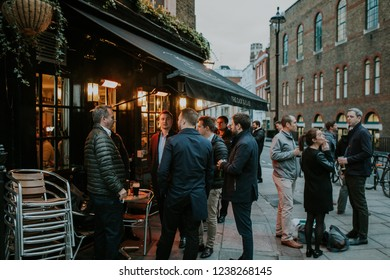 LONDON, ENGLAND - 25th October, 2018: A group of friends having a drink together at an english pub terrace, at evening, in London city, England.