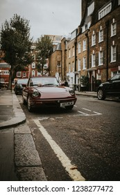 LONDON, ENGLAND - 25th October, 2018: A vintage brown convertible Alfa Romeo Spider from 80's car parked in an exclusive residential street in London city, England.