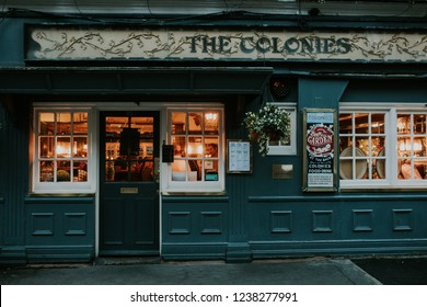 LONDON, ENGLAND - 25th October, 2018: Traditional english tavern facade at evening, with people and lights inside, in London, England.