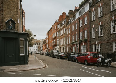 LONDON, ENGLAND - 25th October, 2018: A classical english street in City of Wesminster with houses and car parked in row, in London, England.