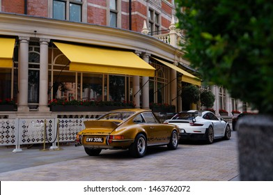 London, England - 27 July 2019: Two rare Porsche sports cars parking in front of The Connaught hotel, in Mayfair. The exact models: a yellow Porsche 911 Carrera 2.7 RS, and a white 911(991) GT2RS.