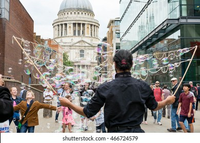 London, England - 28 July 2016 : Street performer entertain tourists and children by huge bubbles in front of St.Pail Cathedral . on 28 July 2016 in London, United Kingdom