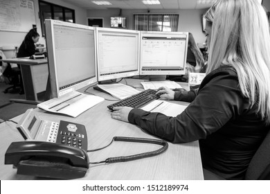 London, England, 28/01/2019 Black and White image of young woman call girl in an administrative role admin work for corporate company in modern office typing on the computer and answering phone calls