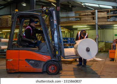 London, England, 28/01/2019 Colour image of a forklift lifting wooden pallet onto a rotating industrial lazy Susan for wrapping a stack of boxes together in plastic wrap. Keeping product safe