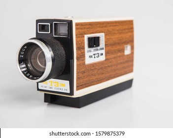 London, England, 29/11/19 Vintage retro Prinz T3 16mm 8mm video movie camera. shot on a studio background isolated on white. Beige wood trim old school style media production with kodak film