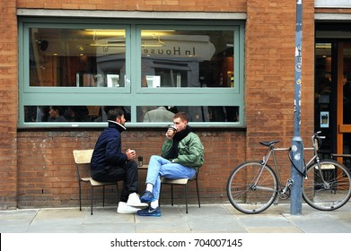 LONDON, ENGLAND- 4 JANUARY 2015: Two undefined men chatting outside the coffee shop with a bike against the pillar in the Shoreditch which is  the north-eastern corner of the City of London, England