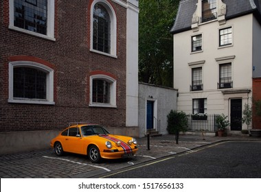 London, England - 5 September 2018: A bright orange Porsche 911 T parking in the elegant Mayfair, London. This old German sports car is from the 1970's.