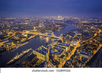London, England - Aerial Skyline view of London. This view includes the Tower of London, the iconic Tower Bridge, HMS Belfast ship and skyscrapers of Canary Wharf at blue hour