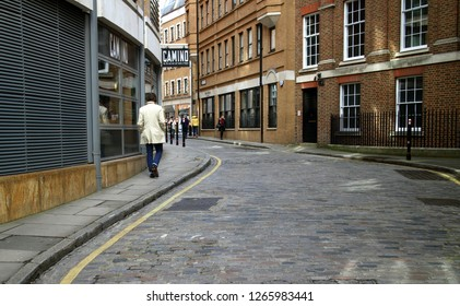 London, England - April 02, 2015: Pedestrians pass along a typical cobblestone street with old and new buildings on either side in London, England