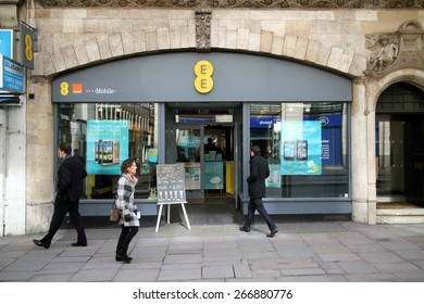 London, England - April 02, 2015: People passing and entering an EE store in London, England. EE delivers mobile and fixed communications services and includes the Orange and T-Mobile companies