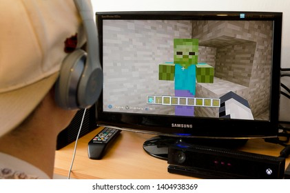 London, England - April 07, 2015: Teenager playing Minecraft video game, Minecraft was released in 2011 and became popular worldwide.