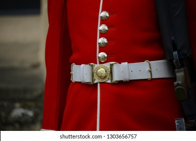 London, England - April 14, 2017: Detail of the golden buttons, belt buckle and red jacket of a Foot Guard, in the fort Tower of London in the United Kingdom