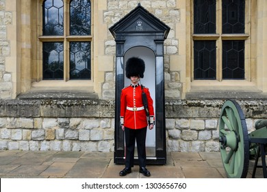 London, England - April 14, 2017: Soldier of the Irish guard belonging to the British Army, also called Foot Guards. He is standing guard next to his gate in the Tower of London, where the Crown J