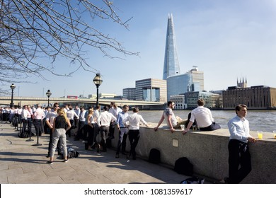 LONDON, ENGLAND - April 19, 2018: Office workers enjoying a drink on the Thames riverside during the warmest day of the year.