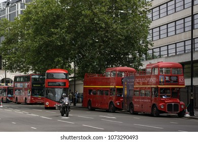 London, England - August 11 2015: Several red London buses of various types - two old buses now used for tourist tours, and two new modern red buses.