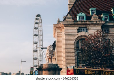 LONDON, ENGLAND - August 16, 2016: London Eye near River Thames with Lion statue on the background Lodon, England