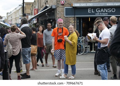 LONDON, ENGLAND - August 20, 2017 local people. Mother in a long yellow coffee and son in an orange T-shirt with pink hair during a market on Broadway Road. The motley crowd wanders past
