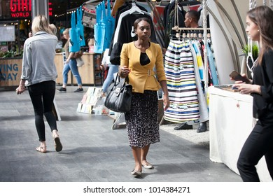 LONDON, ENGLAND - AUGUST 22, 2017 A woman in a yellow sweatshirt and a multicolored skirt goes through the market