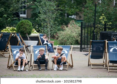 LONDON, ENGLAND - AUGUST 22, 2017 Three boys six years old are eating ice cream sitting on deckchairs in the park
