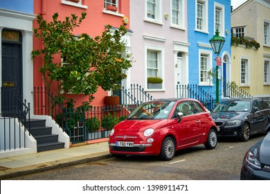 London / England - August 23 2018: Red Fiat 500 in beautiful romantic scenery, quiet street with colorful houses during sunny summer day in London. Interesting architecture, residential prime area.