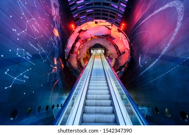 London, England - August 23 2018 - Red globe inside of London Natural History Museum looking up the escalator with great colours and constellations on walls