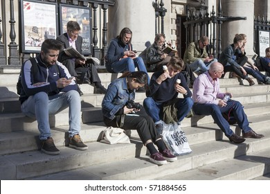 LONDON, ENGLAND - August 25 , 2016 People of all ages are sitting on the steps near Trafalgar Square, relaxing and sunbathing in the sun