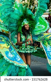LONDON, ENGLAND - AUGUST 26: A street dancer wearing a feathered headdress and costume at Notting Hill Carnival on August 26, 2013 in London