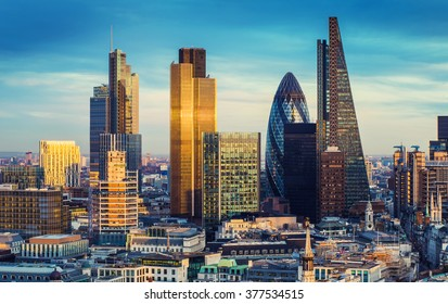 London, England - The bank district of central London with famous skyscrapers and other landmarks at sunset with blue sky - UK