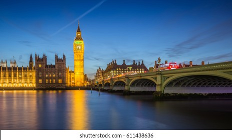 London, England - The Big Ben Clock Tower and Houses of Parliament with iconic red double-decker buses at city of westminster by night