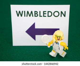 London, England - CIRCA July 2019: A small tennis player figurine in front of a sign for Wimbledon. Symbol for the Wimbledon Tennis Championship. Sign is in purple and green Wimbledon colours.