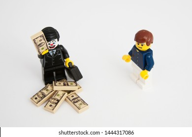 london, england - CIRCA July 2019:Toy manager and worker. Management has all the cash, worker has a frustrated and angry face. Symbolic of salary disparity; banker's bonuses etc.