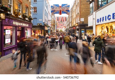 LONDON, ENGLAND - DECEMBER 17: Motion blur of Christmas shoppers on Carnaby Street, London. In London, England. On 17th December 2016.