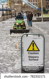 London, England. December 2017. Snow in London with snowplow in action to clear slippery roads and pavement at London Bridge City riverside on the Thames.
