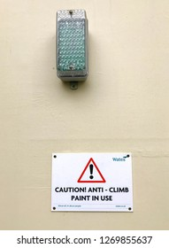 LONDON, ENGLAND - DECEMBER 2018: Security light on wooden fencing aroung a building site with a sign warning of the use of anti climb paint to deter theft and vandalism
