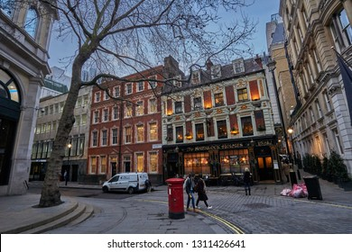 LONDON ENGLAND - FEBRUARY 2017: Beautiful urban scenery in the center of London city. Architectural buildings, British style, and people walking in a typical cold winter day in England United Kingdom.