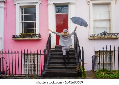 LONDON, ENGLAND - FEBRUARY 2017: Young woman feels happy holding an umbrella in front of  a coloured house in the famous Notting Hill area in a rainy day. London, United Kindom.