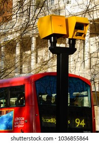 London, England - February 2018: close up view of road traffic speed cameras on a city street with a red bus in the background