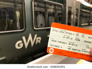 London, England - February 2018: Close up view of a railway ticket with the logo of a railway company in the background