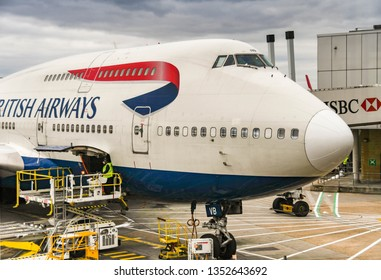 LONDON, ENGLAND - FEBRUARY 2019: Gate Pallet loader and open cargo door ready to load air freight into a British Airways Boeing 747 jet at London Heathrow Airport,