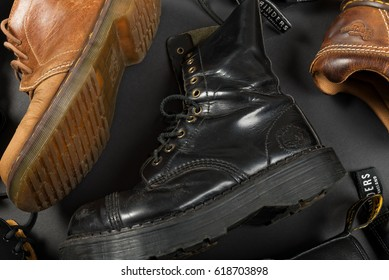 LONDON, ENGLAND - FEBRUARY 4, 2016: Old-fashioned and worn boots on gray background. Classic Dr. Martens models and classic Grinders models.