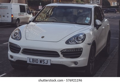 LONDON, ENGLAND - FEBRUARY 6, 2017: View of a white Porsche Cayenne S from the front, close up, parked on a street in London.